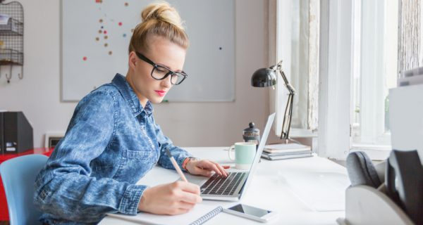 Blonde woman wearing jeans shirt and nerd glasses sitting at the desk in an office and working on laptop.